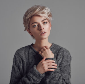 Fashion portrait of young woman with blond short hair isoalted on gray background