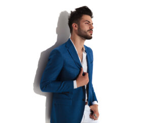 Sensual young man looking to the side and adjusting his jacket while holding on of his hand in his pocket and wearing a blue suit, leaning on white studio background