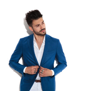 Mystified man curiously looking to the side and adjusting his jacket while wearing a blue suit and standing on white studio background