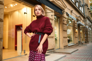 Beautiful stylish blond girl in knitted sweater confidently looking in camera on city street