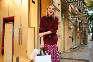 Cheerful stylish blond girl in knitted sweater with shopping bags joyfully looking in camera after shopping outdoor