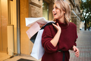 Attractive casual blond girl in knitted sweater with shopping bags on shoulder happily looking away on city street