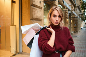 Attractive stylish blond girl in knitted sweater with shopping bags confidently looking in camera after shopping on city street