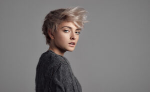 Fashion portrait of female model with blond short hair wear sweater