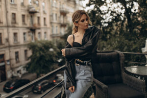 Stylish fashionable blonde woman with smoky eye make-up, in jeans, lingerie and black leather jacket dancing on a balcony in the city. Spring autumn fashion concept. Soft selective focus.