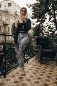 Stylish fashionable blonde woman with smoky eye makeup, in jeans, lingerie and black leather jacket on the balcony in the city. Spring autumn fashion concept. Soft selective focus.