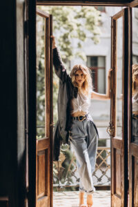 Stylish fashionable blonde woman with smoky eye makeup, in jeans, white T-shirt and black leather jacket on the balcony in the doorway.Spring autumn fashion concept.Soft selective focus.