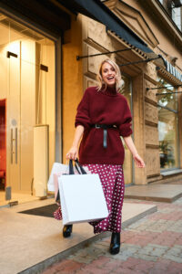 Attractive joyful blond girl in knitted sweater with shopping bags happily looking in camera after shopping outdoor